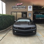 Black Camaro in front of shop