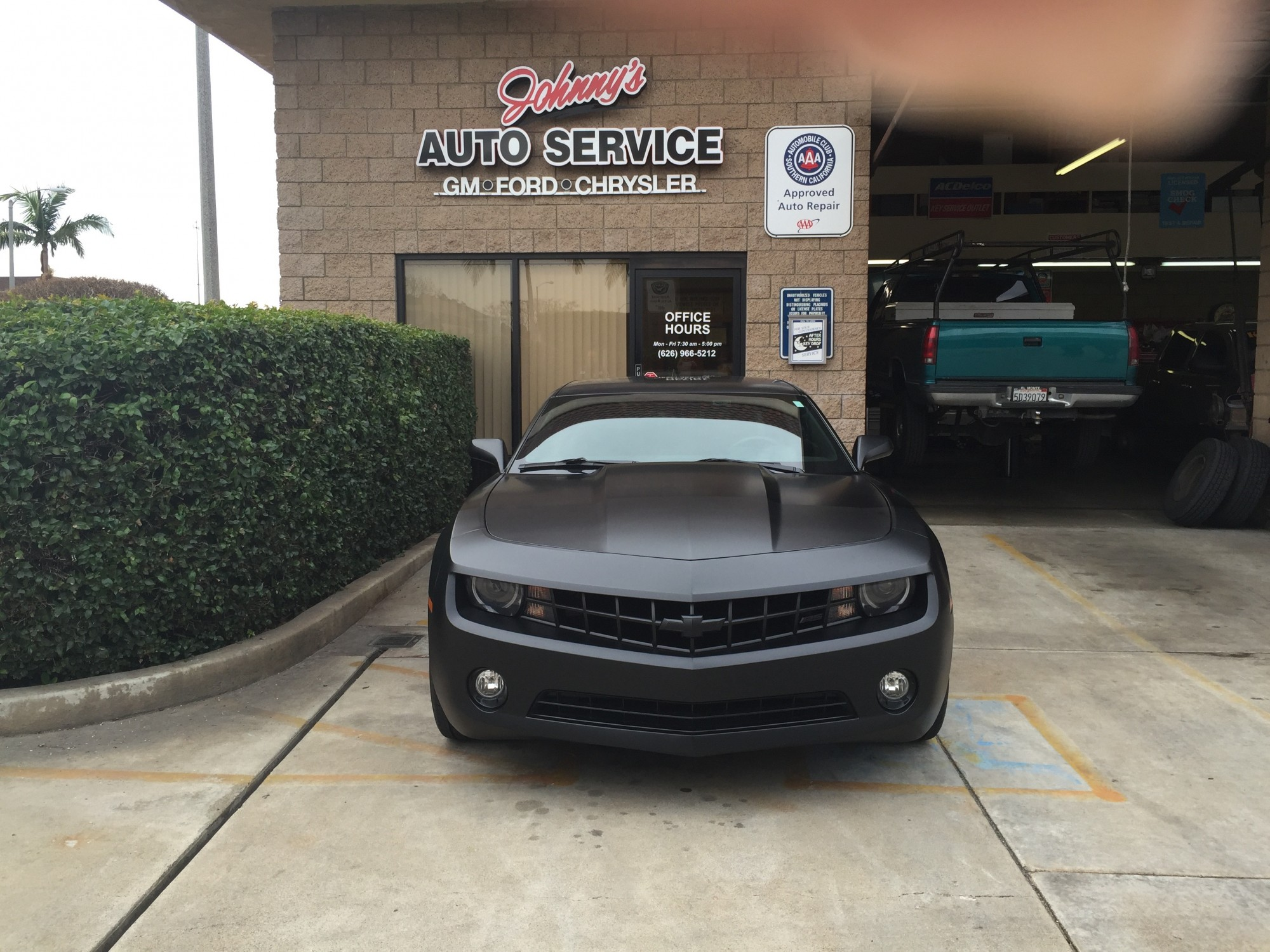 Black Camaro in front of shop